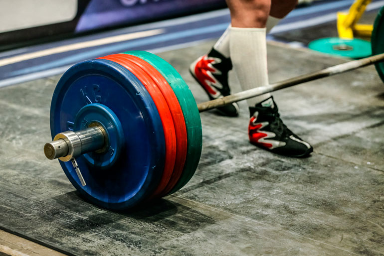 barbell is loaded with rubber plates