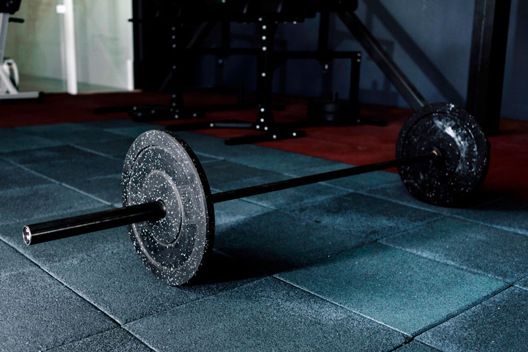 barbell with plates on tiled floor