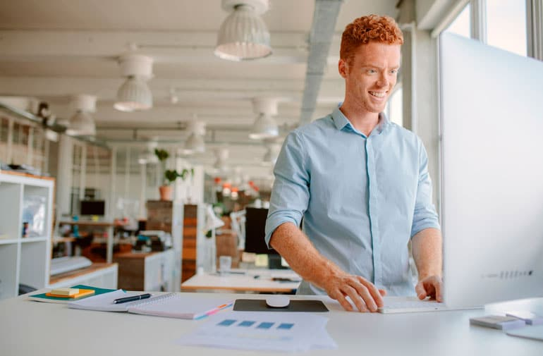 cheerful man is focused on working at desk