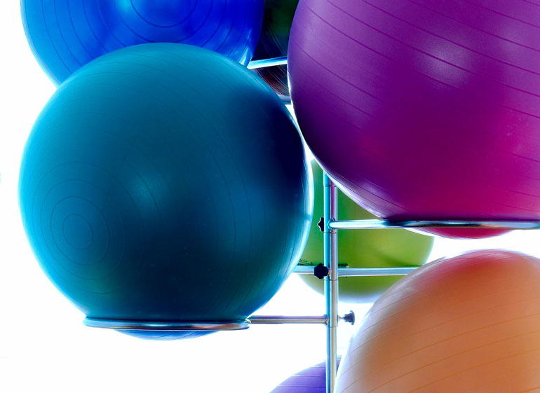 colorful exercise balls are on racks