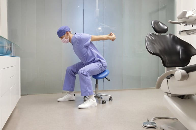 dentist is stretching on saddle stool