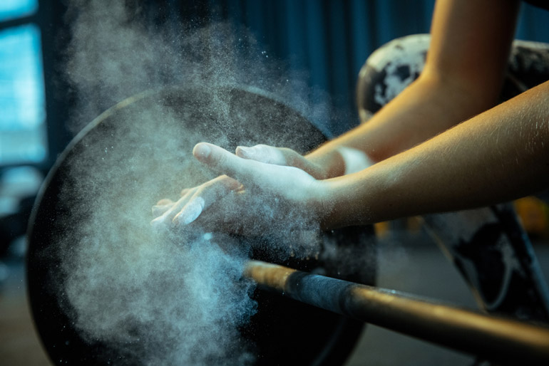 hands in gym chalk to hold barbell