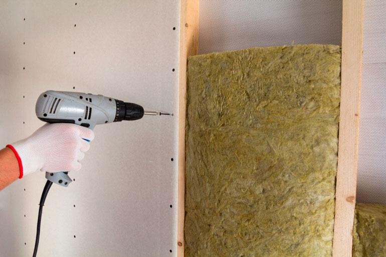 handy man is installing drywall