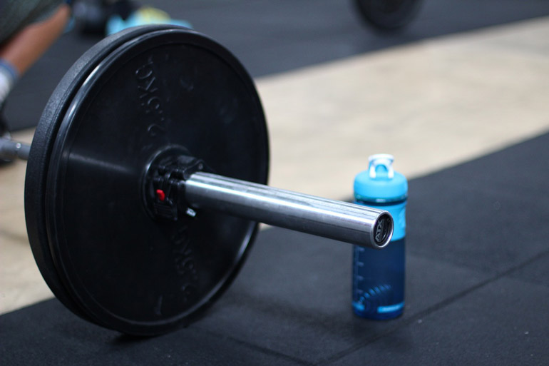 loaded barbell and water bottle on the floor