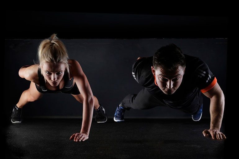 man and woman are doing push ups