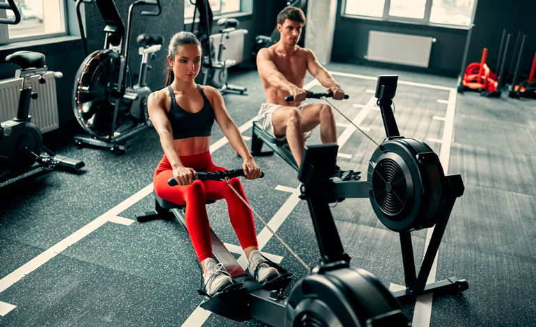 man and woman working out on rowing machines