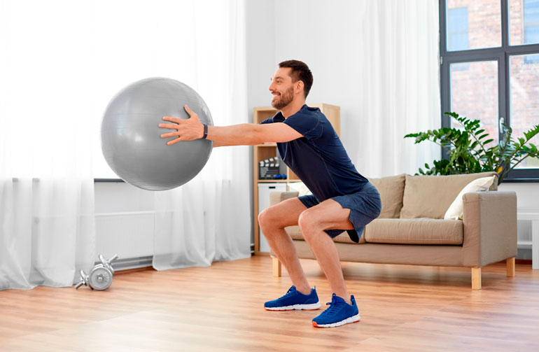 man doing squats with exercise ball