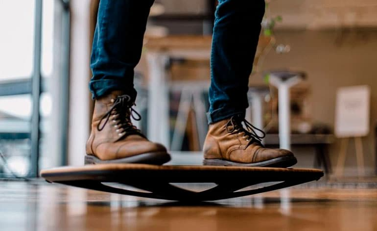 man in boots is standing on balance board