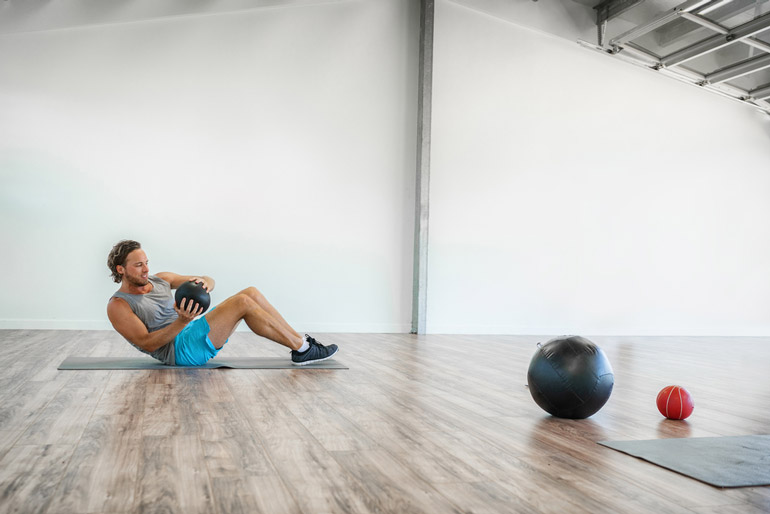 man is doing crunches with medicine ball
