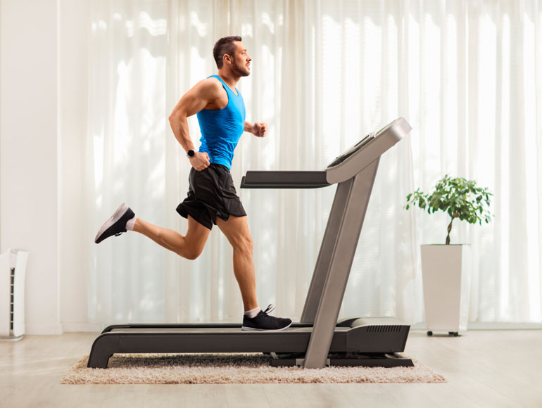 man is exercising on treadmill at home