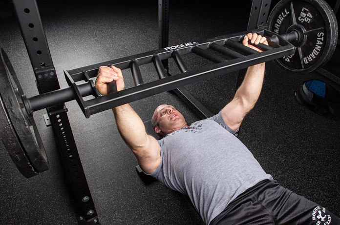 man is exercising with Swiss barbell