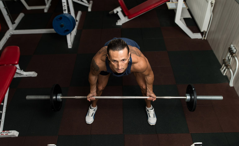 man is performing barbell rows at home