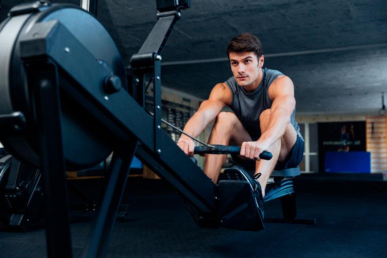 man is pulling handle on rower machine