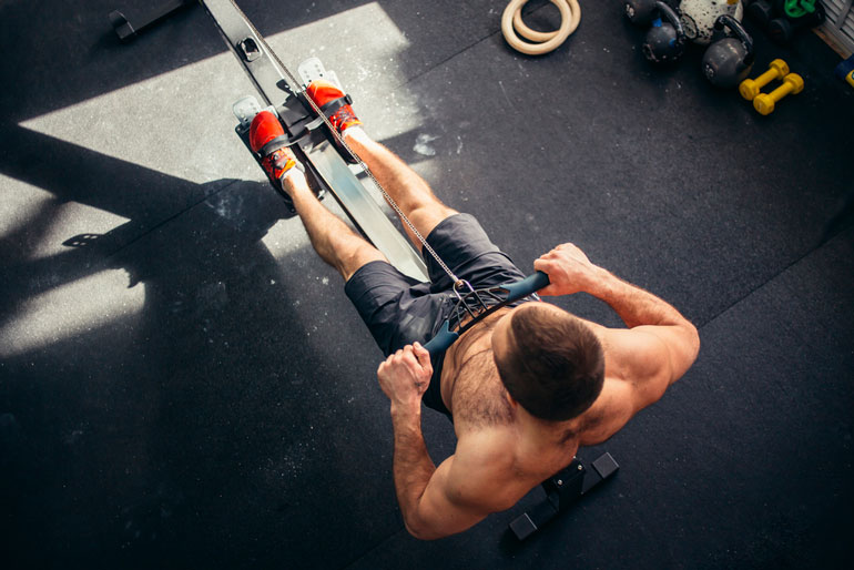man is pulling handle on rowing machine close view