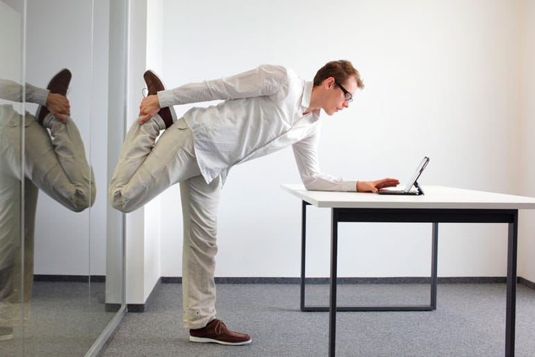 man is stretching at the desk