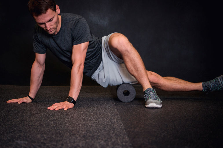 man is stretching with a foam roller