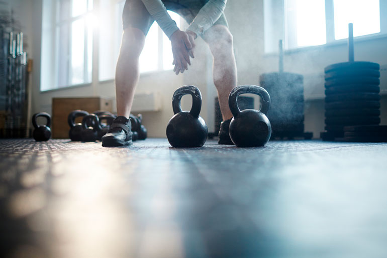 man is working out with kettlebells