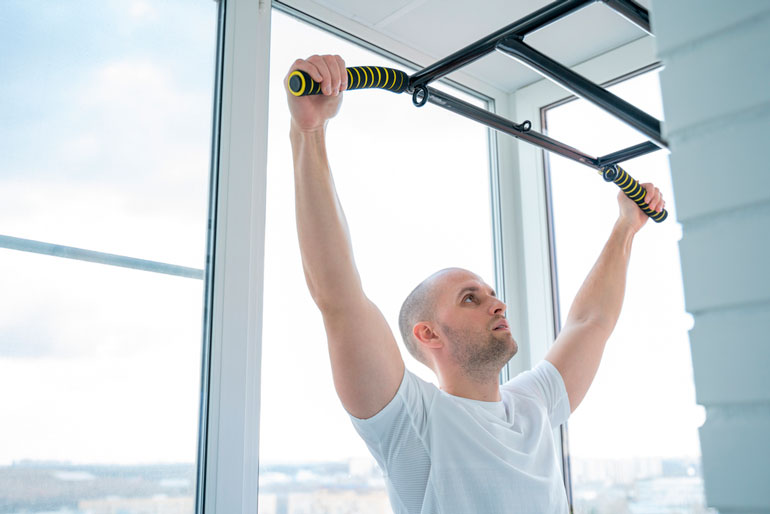 man is working out with pull up bar