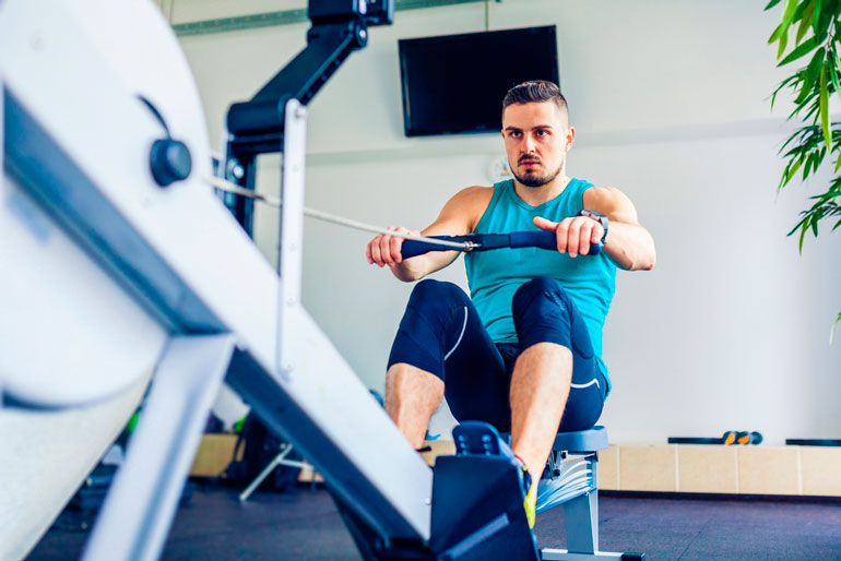 man is working out with rowing machine