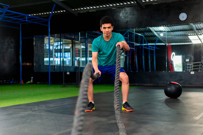 man is working with battle ropes