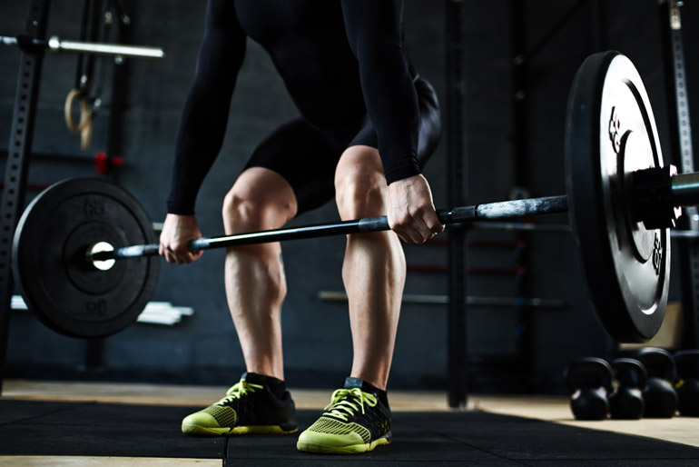 man lifting barbell to the knees
