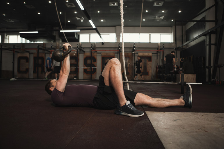 man lying with raised kettlebell