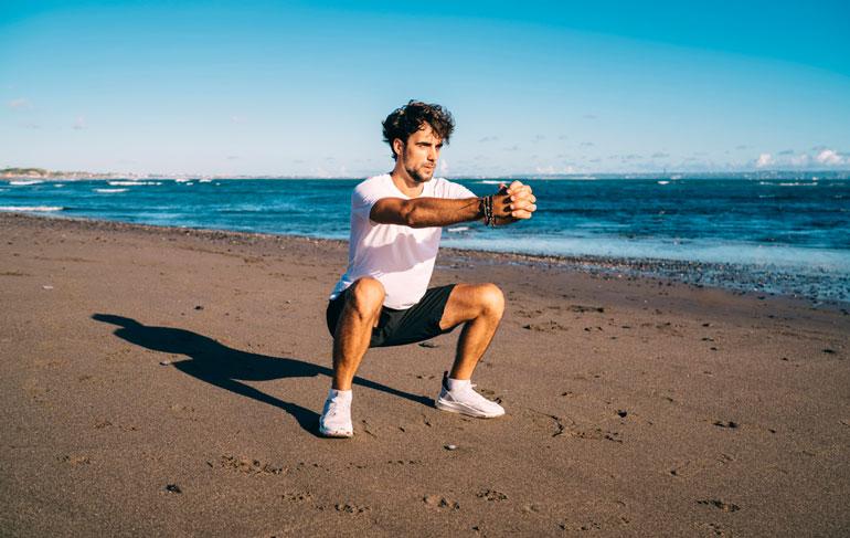 man performing Air Squat at beach