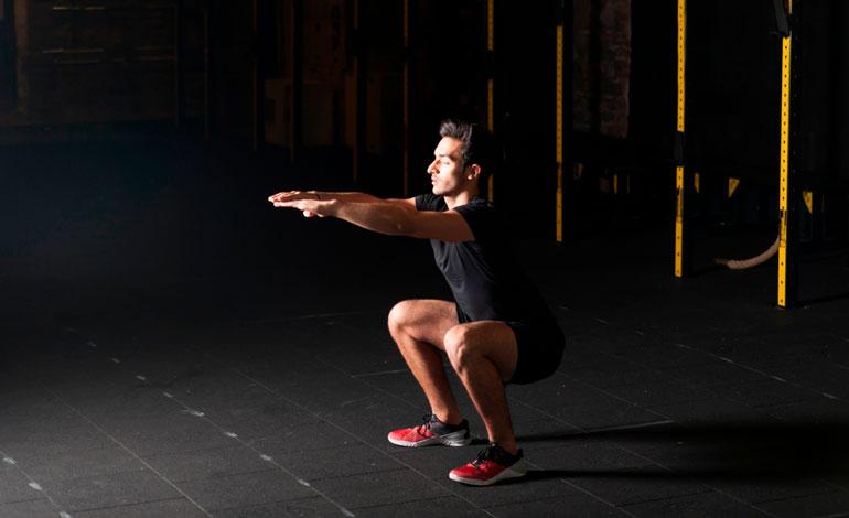 man performing Air Squat at gym