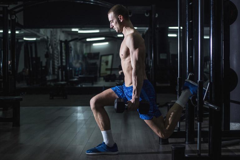 man performing Bulgarian Split Squat at gym