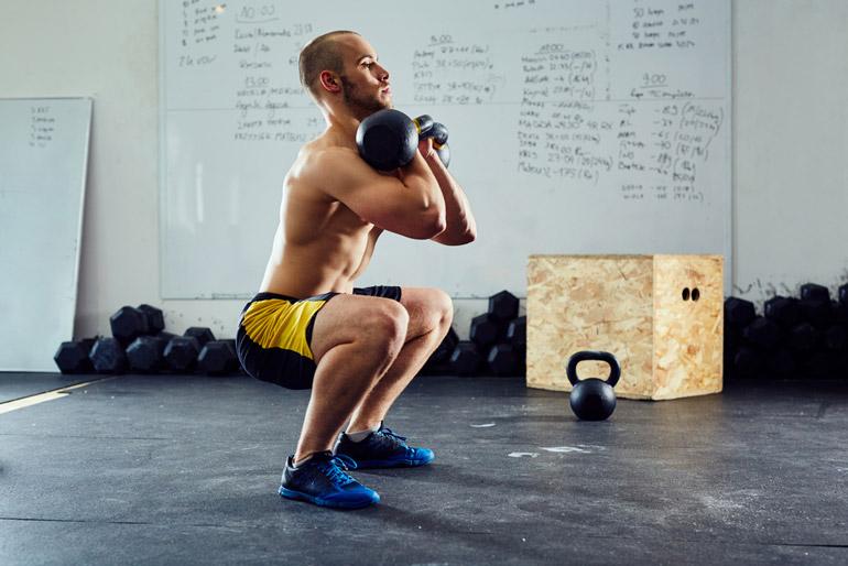 man performing Kettlebell Squat Thrust