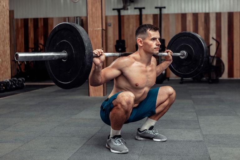 man performing barbell Squat at gym