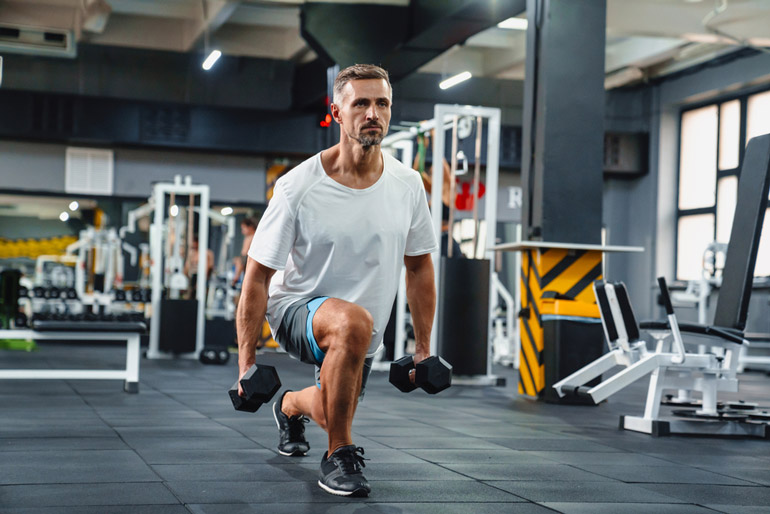 man performing lunges with dumbbells