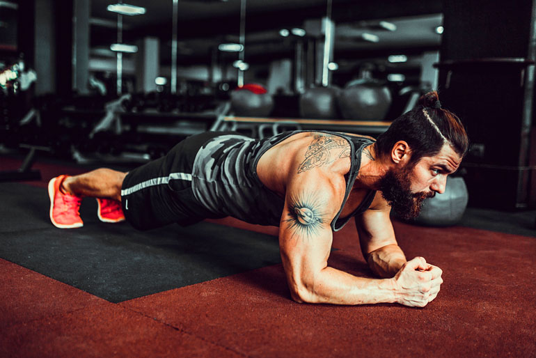 man standing in plank at gym