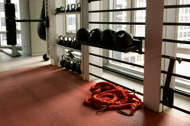 orange battle ropes are dropped on floor