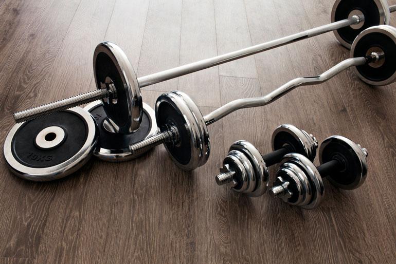 set of barbells on wooden floor