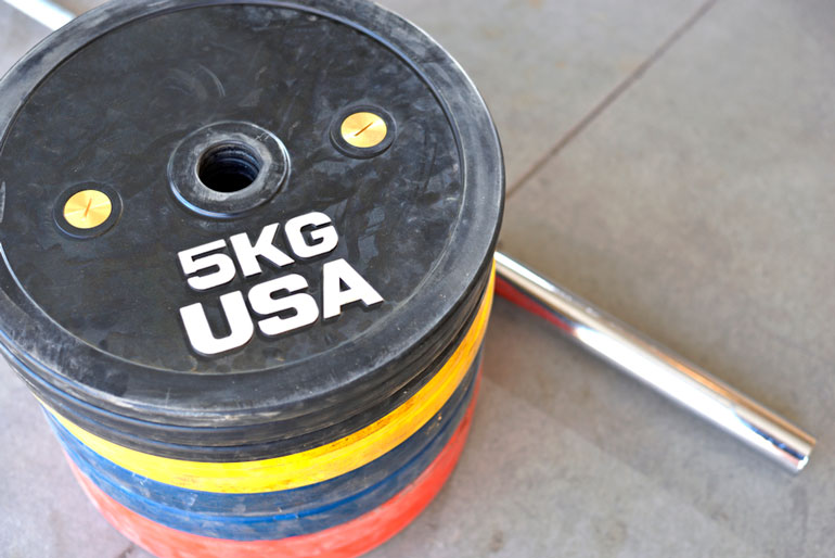 stack of bumper plates with barbell