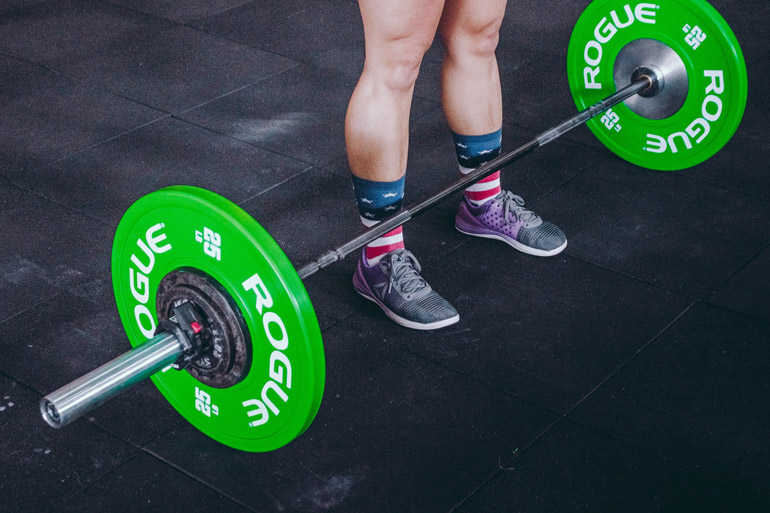 straight barbell with green rubber plates