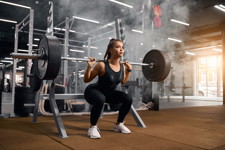 woman is Powerlifting with barbell