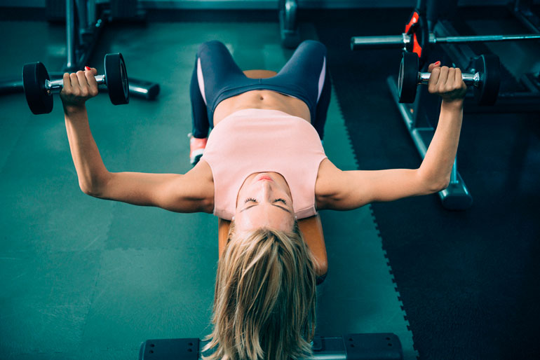 woman is doing Bench Press at gym