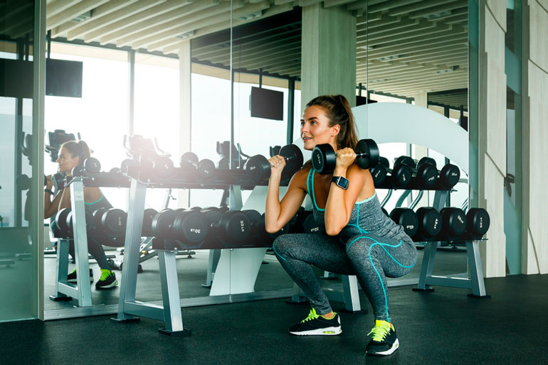 woman is doing Front Squat with dumbbells