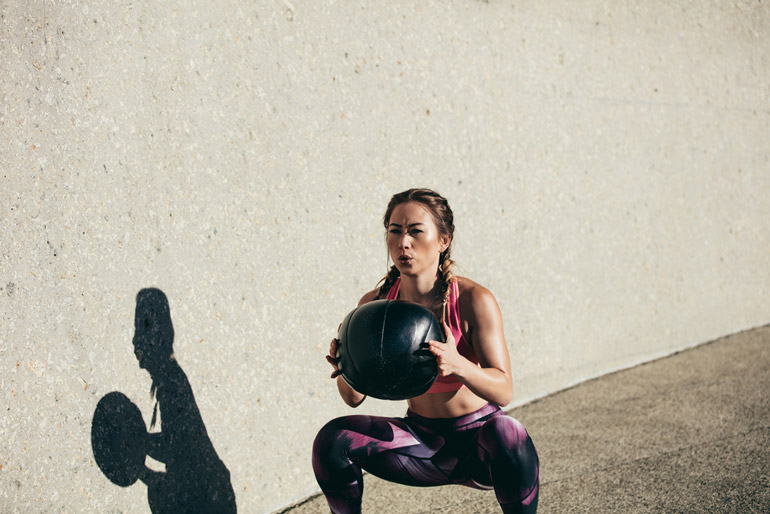 woman is doing Goblet Squat with a Medicine Ball
