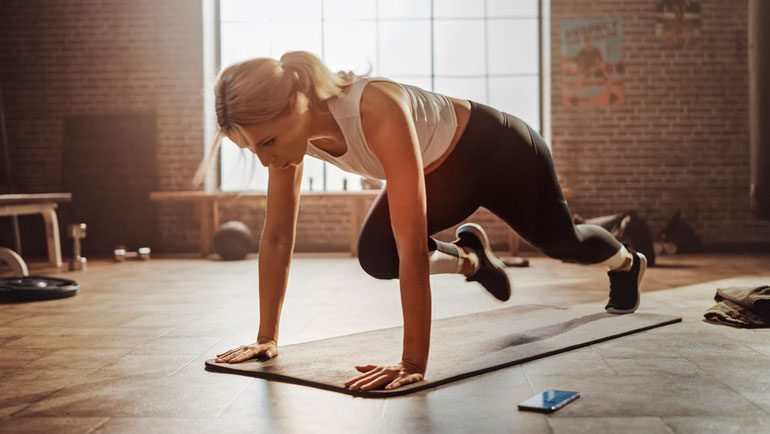 woman is doing Mountain Climbers on mat