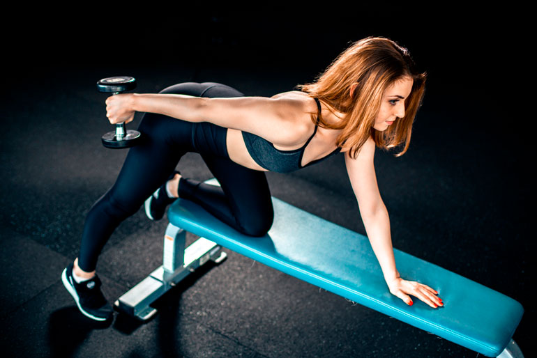 woman is doing Tricep Kick Back on bench