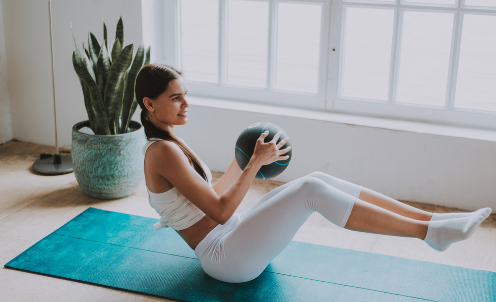 woman is doing crunches with medicine ball