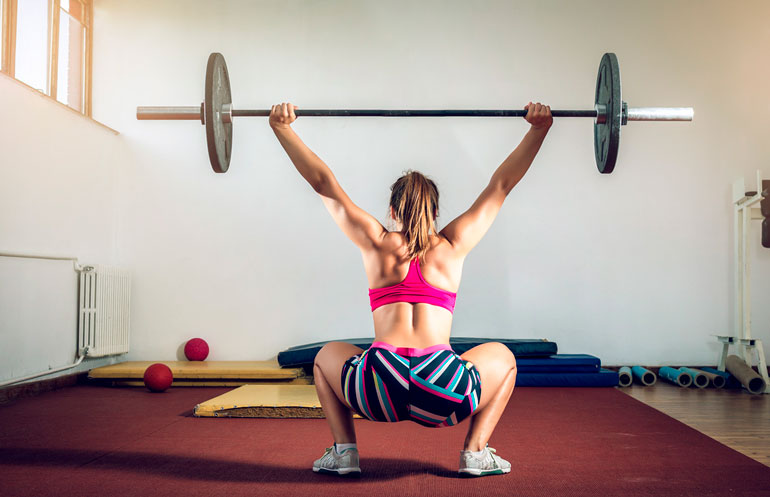 woman is doing squats with a barbell