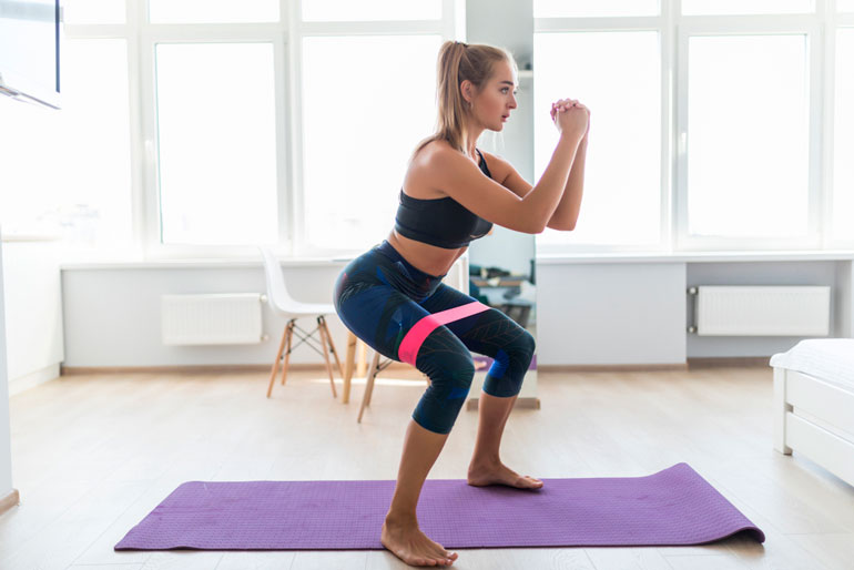 woman is doing squats with a pink resistance band