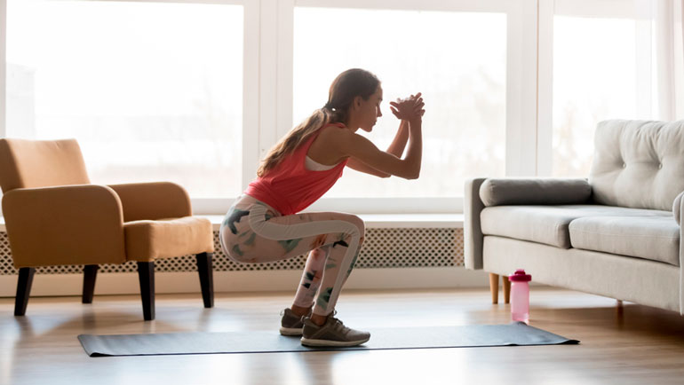 woman is exercising in front of couch