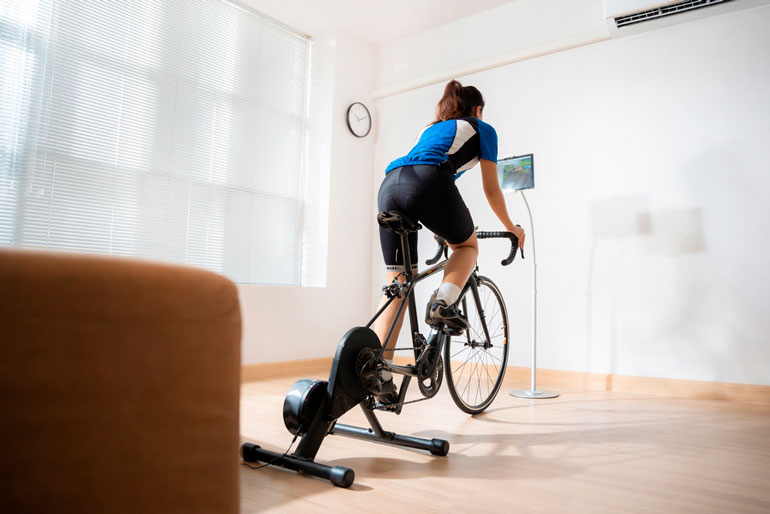 woman is exercising on cycling machine