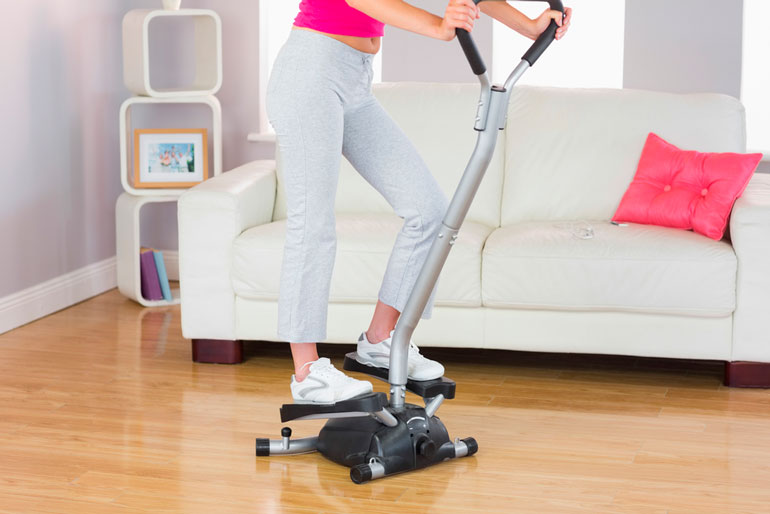 woman is exercising on stepper at home