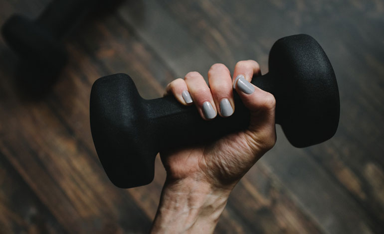 woman is holding black neoprene dumbbell